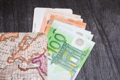 Χρήματα, εισιτήριο αεροπλάνων και χάρτης Eurobanknotes με το πέρασμα τροφής και το χάρτη, στο μαύρο ξύλινο υπόβαθρο Στοκ Φωτογραφίες