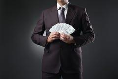 Χρήματα εκμετάλλευσης επιχειρηματιών στα χέρια στο σκοτάδι Στοκ εικόνα με δικαίωμα ελεύθερης χρήσης