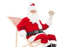 Χρήματα εκμετάλλευσης Santa που κάθονται σε μια καρέκλα αργοσχόλων Στοκ Φωτογραφίες