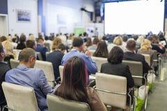 χρήματα εννοιών επιχειρησιακών υπολογιστών Άνθρωποι στη διάσκεψη που ακούει τους ομιλητές οικοδεσποτών στη σκηνή Στοκ Εικόνα