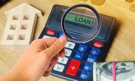Χρήματα και σπίτια στον πίνακα και έναν υπολογιστή με το δάνειο λέξης Η έννοια της αγοράς της ιδιοκτησίας στο χρέος Ανάλυση των δ στοκ εικόνα