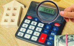 Χρήματα και σπίτια στον πίνακα και έναν υπολογιστή με το χρέος λέξης Η έννοια της αγοράς της ιδιοκτησίας στο χρέος Ανάλυση των δα στοκ εικόνες