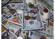 χρήματα $100 και υπόβαθρο νομισμάτων στοκ εικόνα