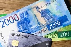 Χρήματα και sberbank πιστωτική κάρτα σε ένα ξύλινο υπόβαθρο στοκ εικόνες