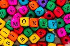 Χρήματα ` λέξης ` των χρωματισμένων ξύλινων κύβων στοκ φωτογραφία