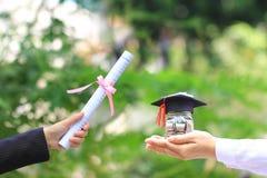 Χρήματα νομισμάτων εκμετάλλευσης χεριών γυναικών στο μπουκάλι γυαλιού με τους πτυχιούχους εκτάριο στοκ εικόνα με δικαίωμα ελεύθερης χρήσης