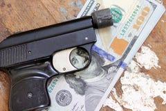 Χρήματα λογαριασμών δολαρίων με το πιστόλι Στοκ εικόνα με δικαίωμα ελεύθερης χρήσης