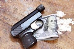Χρήματα λογαριασμών δολαρίων με το πιστόλι Στοκ Εικόνες