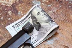Χρήματα λογαριασμών δολαρίων με το πιστόλι Στοκ εικόνες με δικαίωμα ελεύθερης χρήσης