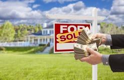 Χρήματα παράδοσης ατόμων στο μπροστινά πωλημένα σπίτι και το σημάδι Στοκ Εικόνες