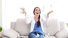 Χρήματα που αφορούν το όμορφο brunette στον καναπέ απόθεμα βίντεο