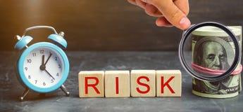 Χρήματα, ρολόι και ξύλινοι φραγμοί με τον κίνδυνο λέξης Η έννοια του οικονομικού κινδύνου Δικαιολογημένοι κίνδυνοι Επένδυση σε έν στοκ φωτογραφίες