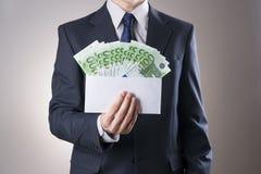 Χρήματα σε έναν φάκελο στα χέρια των ατόμων Στοκ Εικόνες