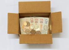 Χρήματα σε ένα συσκευάζοντας κιβώτιο στοκ εικόνες