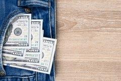 Χρήματα στην τσέπη μπλε Jean στο ξύλινο υπόβαθρο με το αντίγραφο spac Στοκ Φωτογραφίες