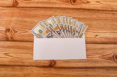 Χρήματα στις μετονομασίες 100 δολαρίων σε έναν άσπρο φάκελο σε έναν ξύλινο πίνακα στοκ φωτογραφία