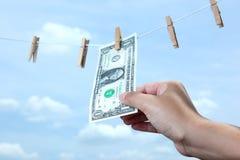 Χρήματα τραβήγματος χεριών από τη γραμμή ενδυμάτων Στοκ εικόνες με δικαίωμα ελεύθερης χρήσης