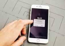 Χρήματα Skrill στο iPhone 7 συν τα προγράμματα εφαρμογών Στοκ Εικόνες
