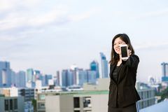 Χρήση επιχειρησιακών ασιατική γυναικών του κινητού τηλεφώνου και παρουσίαση της οθόνης Στοκ φωτογραφία με δικαίωμα ελεύθερης χρήσης