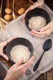Χρήσιμες ξηρές νιφάδες προγευμάτων oatmeal στα κύπελλα που κρατούν δύο ζευγάρια των χεριών στοκ εικόνες με δικαίωμα ελεύθερης χρήσης