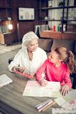Χρήσιμη γιαγιά που βοηθά την εγγονή της που κάνει την εργασία στοκ εικόνες με δικαίωμα ελεύθερης χρήσης