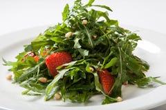 Χρήσιμη σαλάτα φραουλών με τα καρύδια arugula και μέλι στο άσπρο πιάτο Στοκ εικόνες με δικαίωμα ελεύθερης χρήσης
