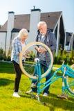 Χρήσιμος αγαπώντας σύζυγος που επισκευάζει το παλαιό μπλε ποδήλατο της ελκυστικής συζύγου του στοκ φωτογραφία