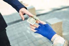 Χρήσιμος ξένος στο μαύρο κοστούμι που δίνει τα χρήματα στους αστέγους Στοκ Φωτογραφία