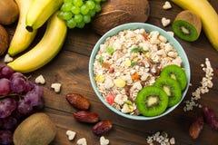 Χρήσιμο muesli δημητριακών προγευμάτων με τους ξηρούς καρπούς σε ένα πιάτο γύρω από τα εξωτικά φρούτα Στοκ εικόνα με δικαίωμα ελεύθερης χρήσης