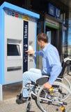 Χρήστης αναπηρικών καρεκλών σε μια μηχανή εισιτηρίων Στοκ φωτογραφία με δικαίωμα ελεύθερης χρήσης