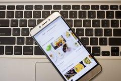 Χρήστης Uber που ανοίγει Uber App στο Smartphone του για να πάρει τα τρόφιμα del Στοκ Εικόνες