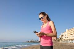 Χρησιμοποίηση γυναικών κινητή στην παραλία με το μεγάλο διάστημα αντιγράφων Στοκ εικόνες με δικαίωμα ελεύθερης χρήσης
