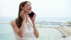 Χρησιμοποίηση γυναικών κινητή στο μπαλκόνι Θηλυκό στις διακοπές που μιλά με το φίλο μέσω του κινητού τηλεφώνου σε σε αργή κίνηση απόθεμα βίντεο