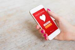 Χρησιμοποίηση γυναικών που χρονολογεί app στο smartphone Στοκ Εικόνες
