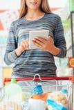 Χρησιμοποίηση γυναικών που ψωνίζει apps στην ταμπλέτα Στοκ εικόνες με δικαίωμα ελεύθερης χρήσης