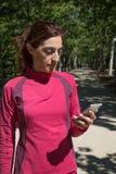 Χρησιμοποίηση γυναικών δρομέων κινητή στην κατακόρυφο πάρκων Στοκ Εικόνα