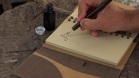Χρησιμοποίηση μιας εκλεκτής ποιότητας μάνδρας πηγών που βυθίζει σε ένα μπουκάλι δοχείων μελανιού που γράφει στην ημερήσια διάταξη φιλμ μικρού μήκους