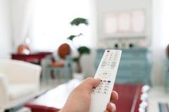 Χρησιμοποίηση του άσπρου τηλεχειρισμού Μετατροπή ή κουμπί προγράμματος που πιέζει στο αριθμητικό πληκτρολόγιο TV φωτεινό καθιστικ στοκ εικόνα με δικαίωμα ελεύθερης χρήσης