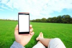 Χρησιμοποίηση του έξυπνου τηλεφώνου με τη φύση Στοκ φωτογραφία με δικαίωμα ελεύθερης χρήσης