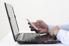 Χρησιμοποίηση του έξυπνων τηλεφώνου και του lap-top Στοκ εικόνα με δικαίωμα ελεύθερης χρήσης
