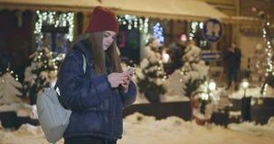 Χρησιμοποίηση του κινητού τηλεφώνου κατά τη διάρκεια του περιπάτου στις οδούς της πόλης νύχτας φιλμ μικρού μήκους
