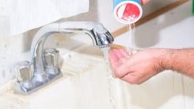Χρησιμοποίηση του νεροχύτη γκαράζ για να πλύνει τα χέρια με το κονιοποιημένο σαπούνι Στοκ Εικόνα
