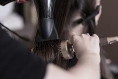 Χρησιμοποίηση του στεγνωτήρα βουρτσών γηα τα μαλλιά και τρίχας Στοκ Εικόνα