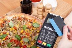 Χρησιμοποίηση του τερματικού πληρωμής με την ανέπαφη πιστωτική κάρτα για την πληρωμή στο εστιατόριο, έννοια χρηματοδότησης, χορτο Στοκ φωτογραφίες με δικαίωμα ελεύθερης χρήσης