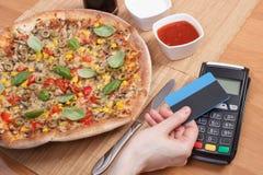 Χρησιμοποίηση του τερματικού πληρωμής με την ανέπαφη πιστωτική κάρτα για την πληρωμή στο εστιατόριο, έννοια χρηματοδότησης, χορτο Στοκ Φωτογραφίες