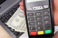 Χρησιμοποίηση του τερματικού πληρωμής, δολάριο νομισμάτων στο lap-top στο υπόβαθρο Στοκ φωτογραφία με δικαίωμα ελεύθερης χρήσης