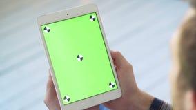 Χρησιμοποίηση του PC ταμπλετών με την πράσινη οθόνη Ένα άτομο κρατά ότι μια έξυπνη ταμπλέτα με το α απόθεμα βίντεο