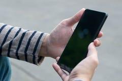 Χρησιμοποίηση του smartphone με το χέρι στοκ εικόνα