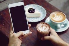 Χρησιμοποίηση του smartphone στον καφέ στοκ εικόνες