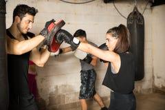 Χρησιμοποίηση των εγκιβωτίζοντας γαντιών πυγμαχίας κατά τη διάρκεια της εγκιβωτίζοντας κατηγορίας Στοκ Εικόνα
